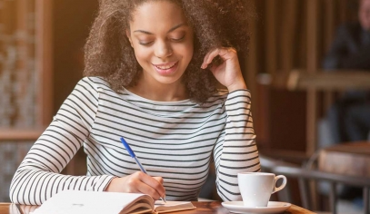 A woman smiles as she writes in her notebook at a coffeeshop