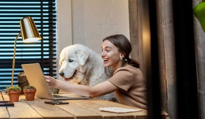 A woman and her dog smiling at her laptop screen