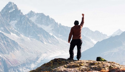 Man with right hand raised on top of a mountain