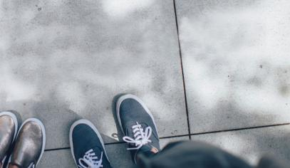 two people standing on gray tile paving