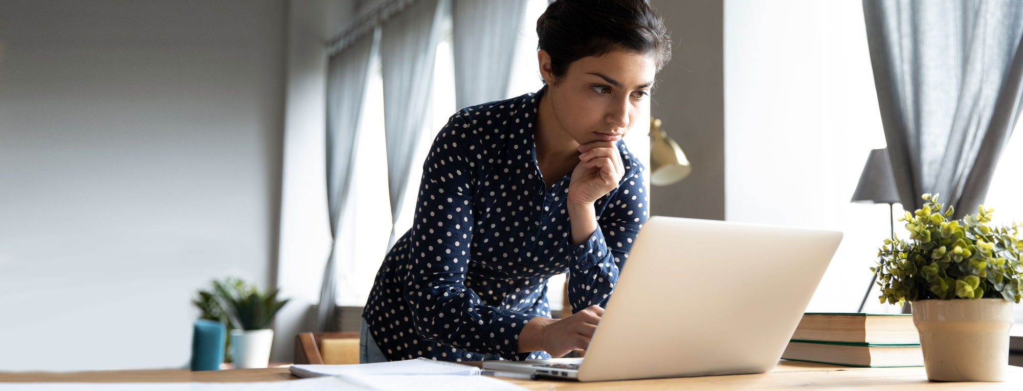 Thoughtful woman working on laptop