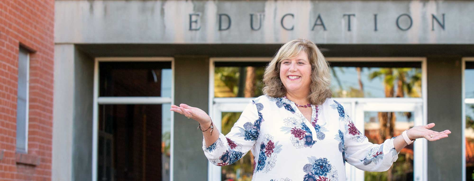 Melody Buckner, Associate Vice Provost of Digital Learning Initiatives and Online Education, stands in front of the education building