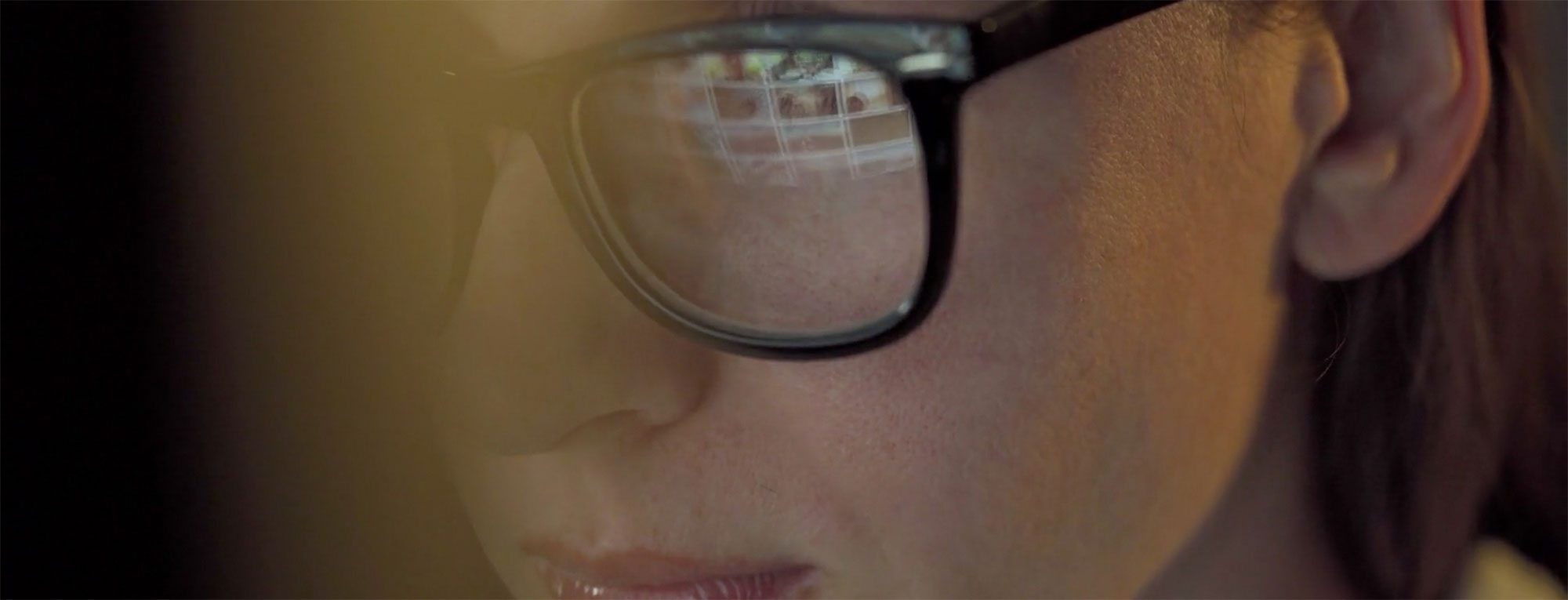Woman with computer screen reflected in glasses
