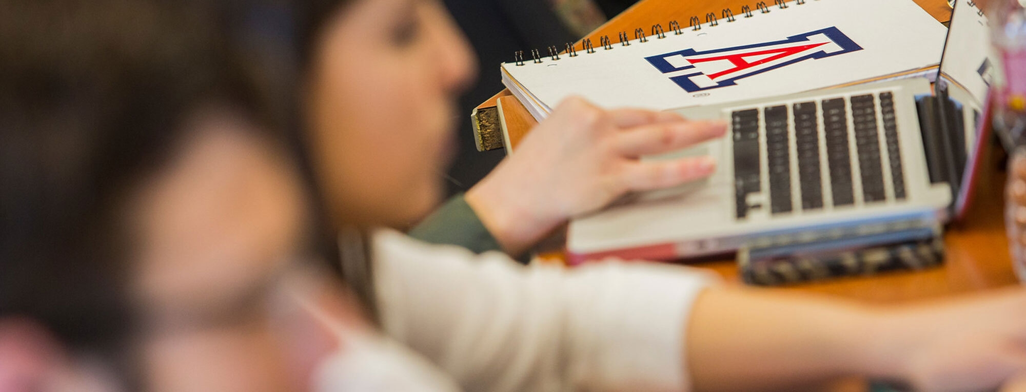 background shows notebook with University of Arizona logo, hand on laptop. Foreground shows two people blurred