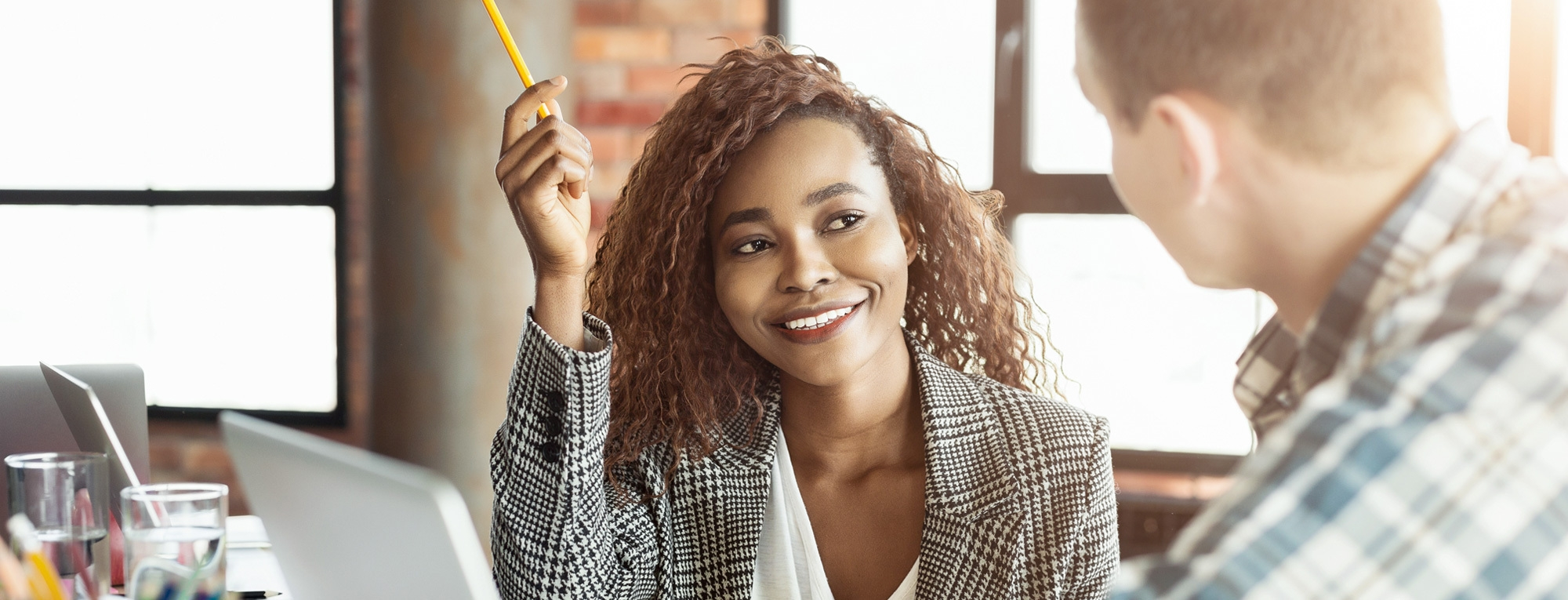 woman smiling and holding a pencil