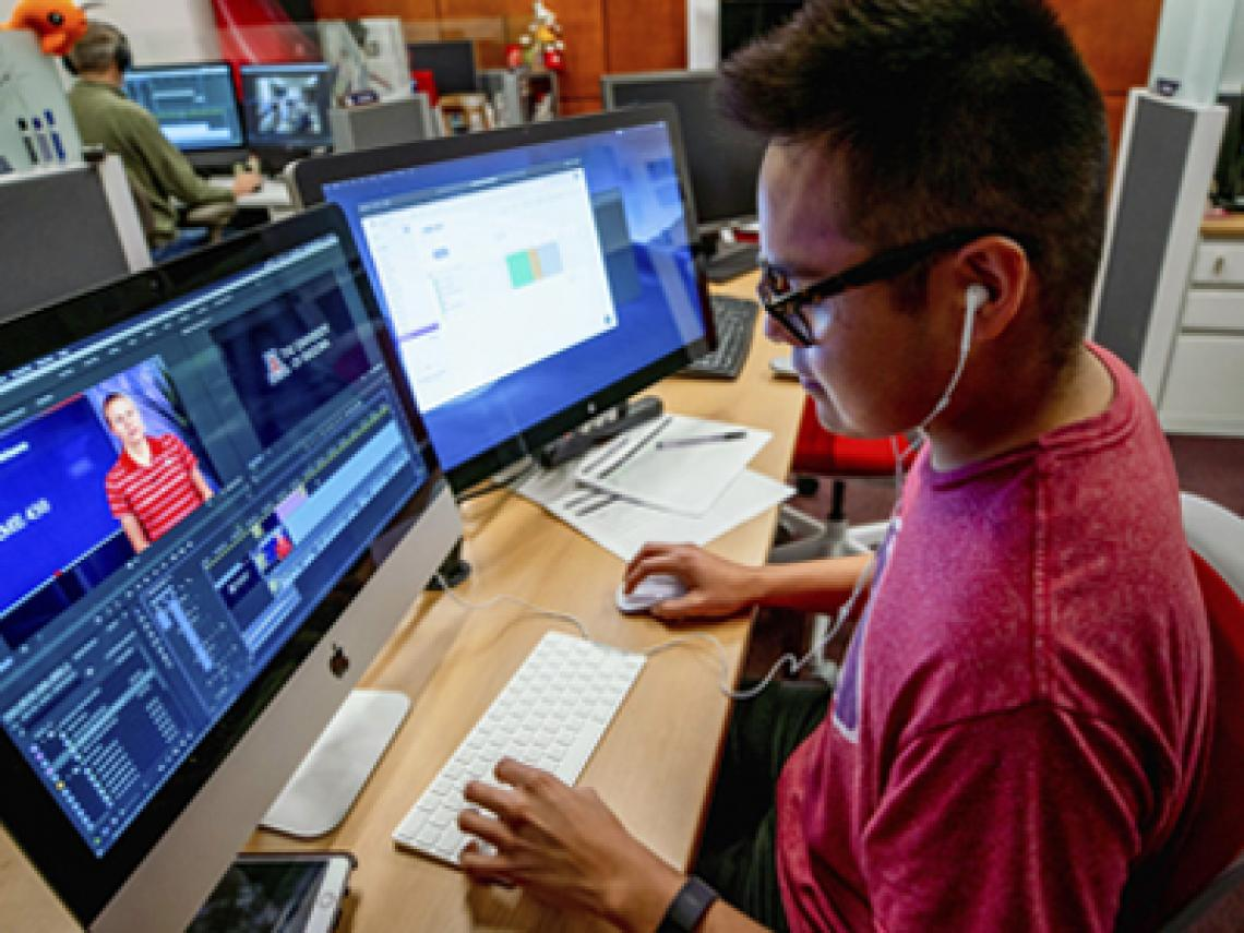 Student Tyler Mann editing a video on his workstation